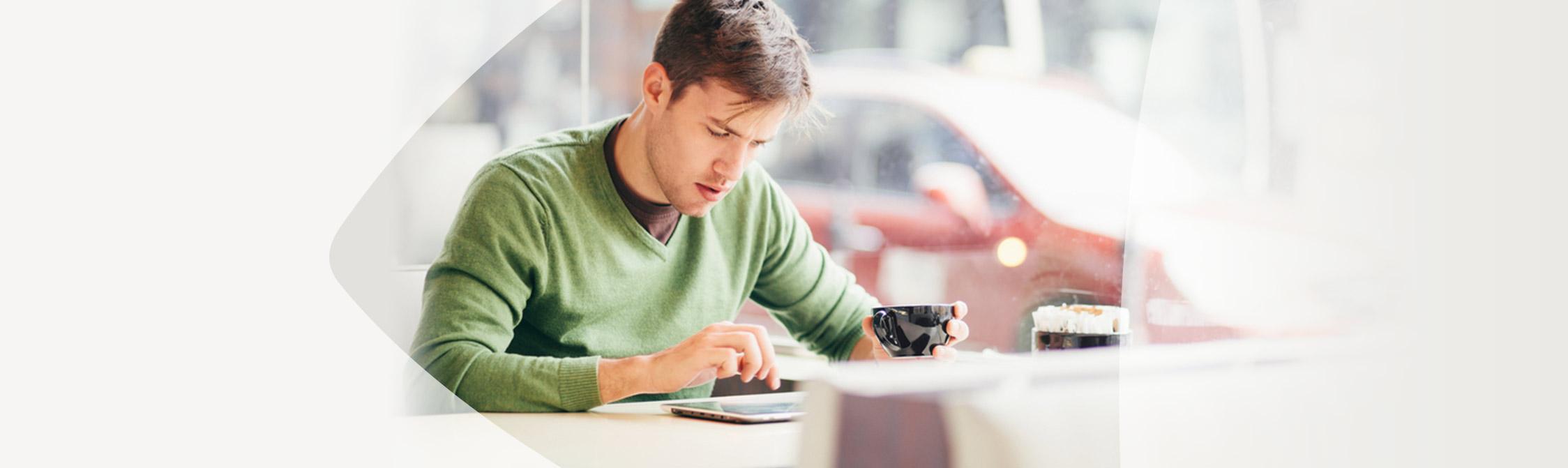 Mann sitzt im Café und informiert sich im Internet