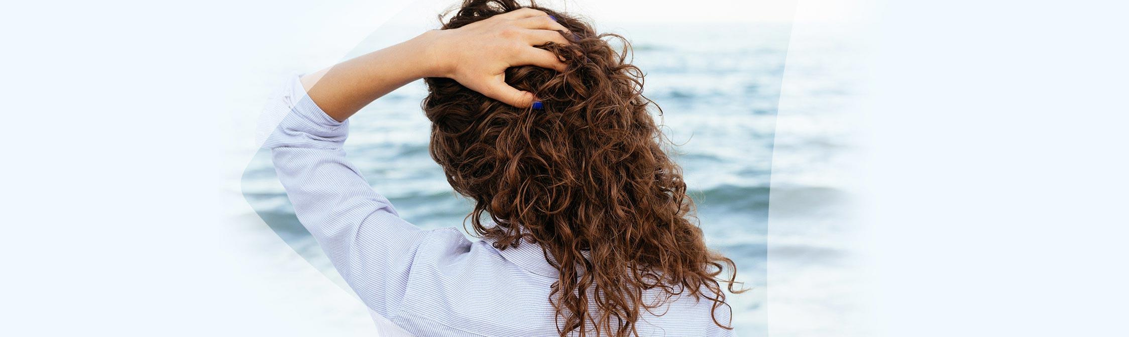 Frau greift sich in die Haare und schaut aufs Meer hinaus