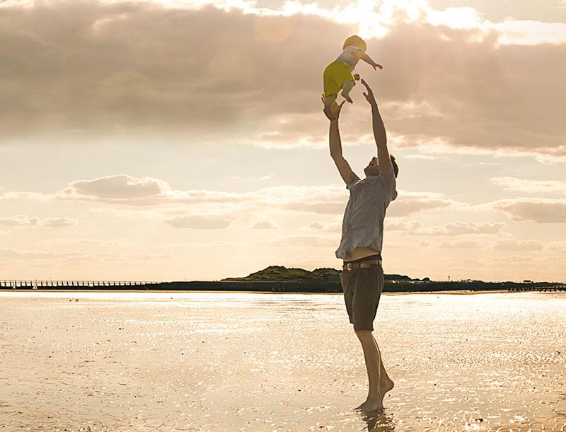 Mann spielt mit Kind am Strand