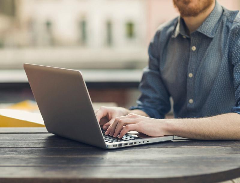 Mann schreibt etwas auf Laptop