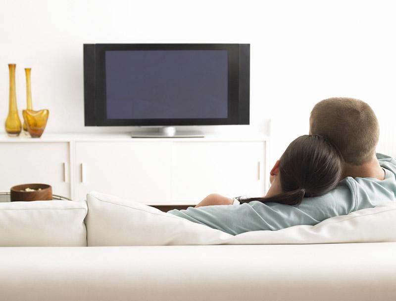 Pärchen sitzt auf der Couch und schaut Fernsehen